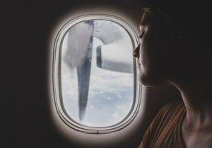 Relocating for the right reasons - woman looking out the window of the airplane when moving abroad