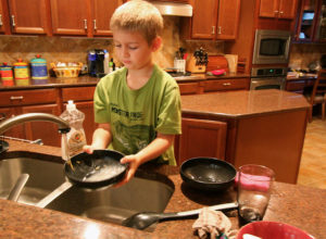 Speed up your household chores - boy washing dishes in the kitchen