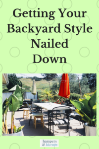 Branching Out? Getting Your Backyard Style Nailed Down backyard patio with table chairs umbrellas large plants privacy fence hamperandhiccups