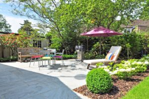 Backyard space with a patio louge chair with umbrella deck chairs bench landscaping