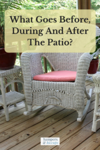 What goes before, during and after the patio? Wicker rocking chair and end tables with potted plants on wood decking patio hampersandhiccups