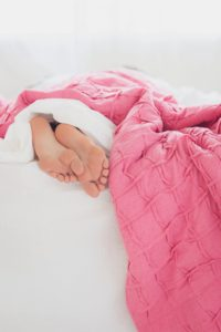 Sleeping better feet sticking out of pink blankets
