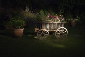 Rustic garden wooden wagon and clay pots of flowers