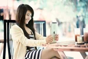 The internet teen girl looking at iPad outside at wooden table