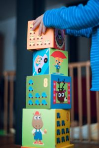 Kids settle into a new house with their old toys unpacked first to play with building blocks toddler hands