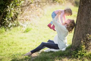 Stress relief tips for your children pregnant mother outside lifting toddler daughter into the air under tree grass