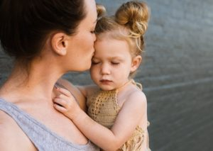 Stress relief tips for children mom kissing daughter's forehead