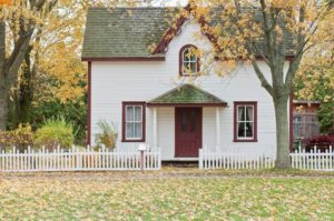 Home Exterior Styles wooden home painted white with red trim with landscaping and white picket fence