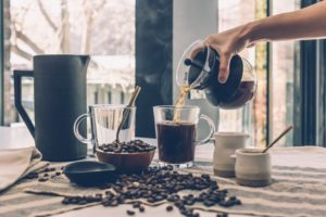 Home sells fast offer coffee to guests at the open house carafe pouring coffee into glass mug coffee beans on counter