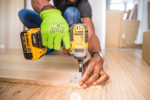Avoid when selling your home ignoring the maintenance issues or trying to diy man using a drill to fix flooring