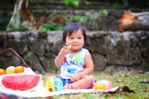 Fussy Eater baby sitting up and eating a banana picnic watermelon ball toy