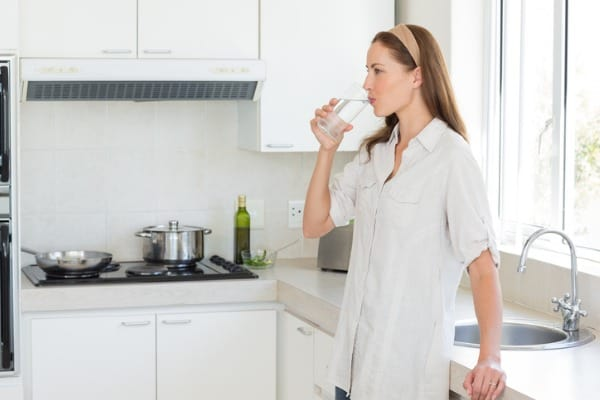 woman drinking glass of water in kitchen