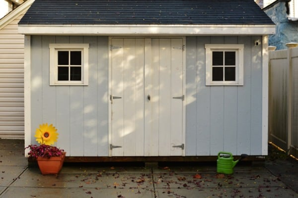 blue-and-white-shed-in-back-yard-of-house-for-storage
