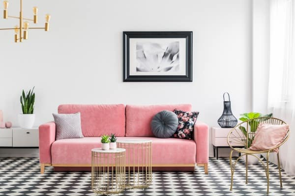 glamour living room interior with a pink sofa golden armchair