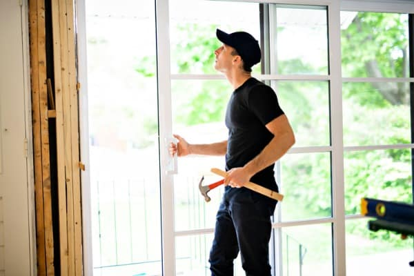 handsome young man installing double sliding patio door in a new