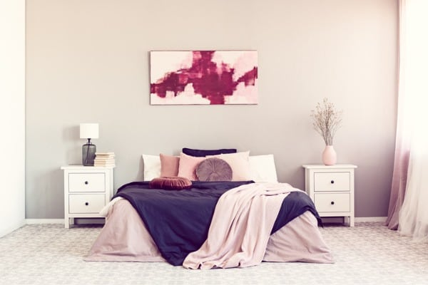 king-size-bed-with-pillows-and-blanket-between-two-wooden-nightstand
