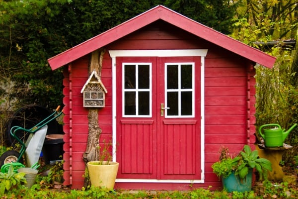 light-red-small-shed-gardenhouse-with-some-garden-tools-around-it