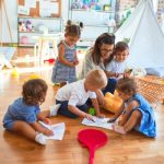 beautiful teacher and group of toddlers sitting on the floor drawing