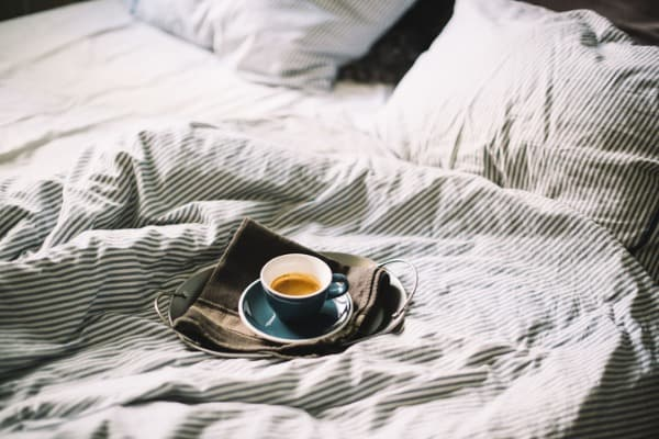 delicious fresh morning espresso coffee in bed in a ceramic blue cup