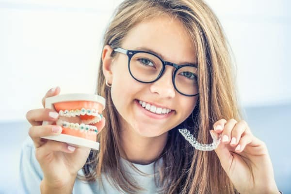 dental invisible braces or silicone trainer in the hands of a young