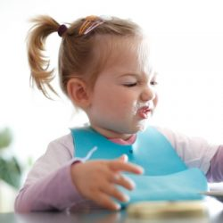 little girl toddler picking her food making faces