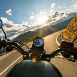 motorcycle driver riding in alpine highway handlebars