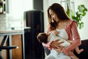 young smiling mother breastfeeding her baby at home