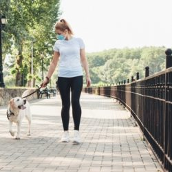 blonde woman and her dog walking in the park while wearing a medical mask