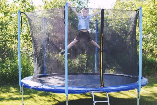 boy jumping on trampoline the child plays on a trampoline outdoor