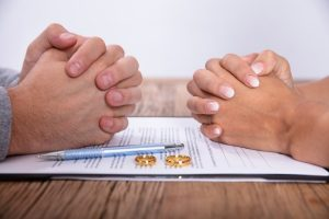 couples hand with divorce agreement and wedding rings