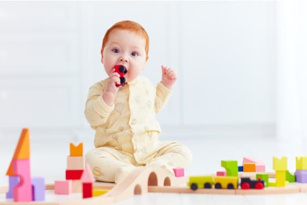cute ginger baby playing with toy railway road at home tasting wagon