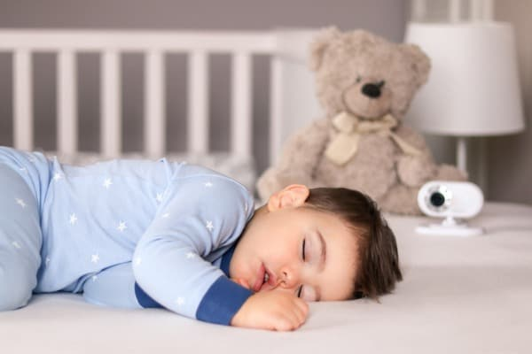 cute little baby boy in light blue pajamas sleeping peacefully on bed