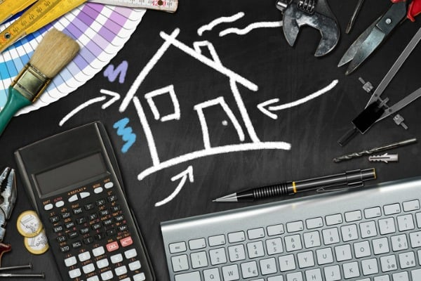home improvement concept work tools and chalk drawing of a house
