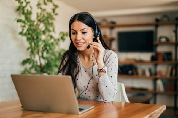 portrait of a cute woman with headset and laptop at home