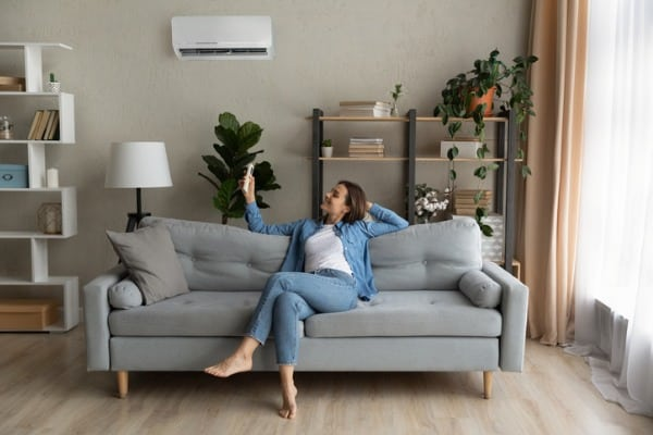 young woman relax on couch turn on ac